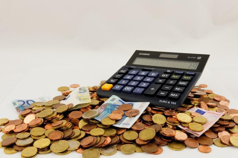 kalkulačka ležící na hromadě mincí a bankovek.jpg