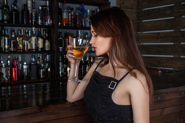 Mladá žena ochutnává víno