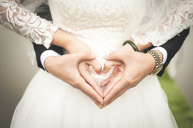 nevěsta se ženichem vytvářejí z prstů srdíčko
