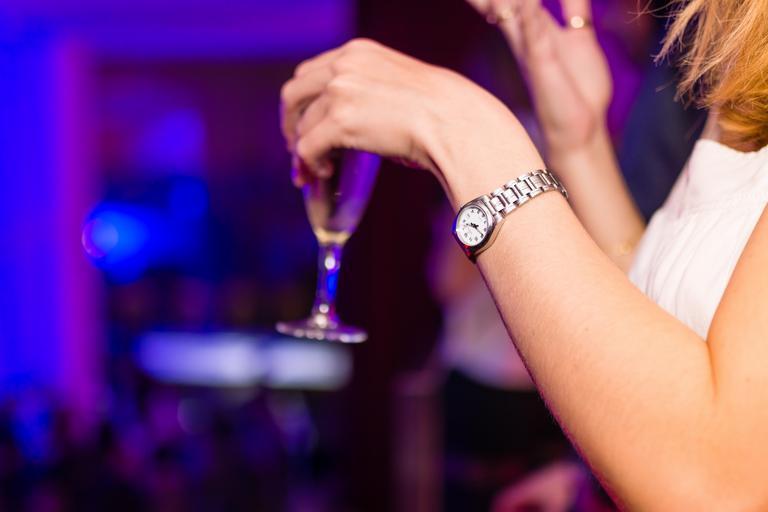 žena v klubu, v ruce drží skleničku s pitím, má hodinky a bílou halenku