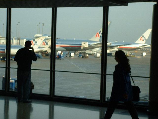 lidé čekající na své lety v čekací hale na letišti